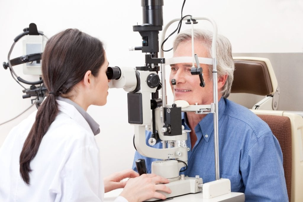 An optometrist or ophthalmologist giving a routine eye exam