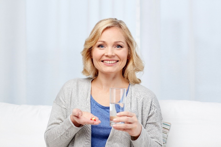 Smiling woman preparing to take her nutritional eye supplements