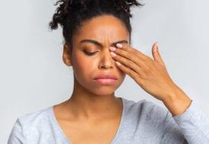 Woman rubs her eye