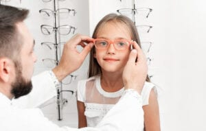A pediatric optometrist places a pair of eyeglasses on a young girl